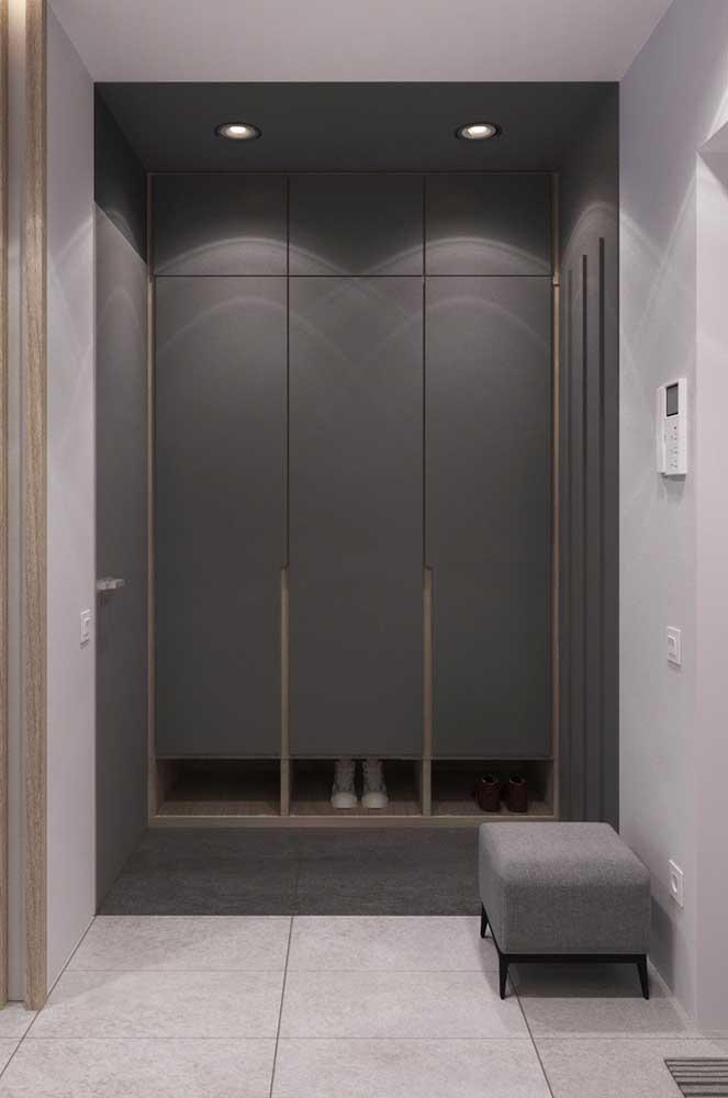 Nesse ambiente, o tom de cinza escuro marca presença no armário e na faixa da parede; junto com ele aparece o branco