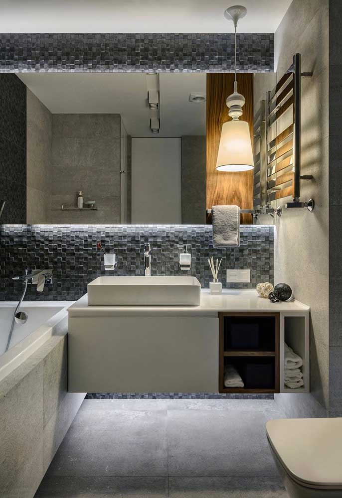 Naturalmente cinza, as pedras revestem e embelezam esse banheiro