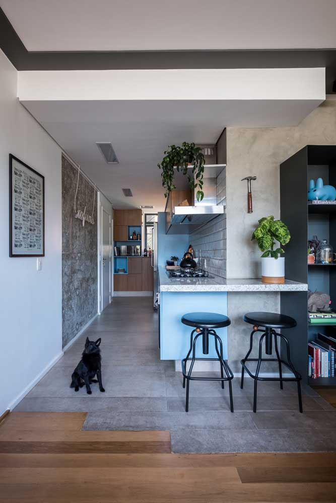 Aqui, o piso cinza ajuda a demarcar a área reservada para cozinha