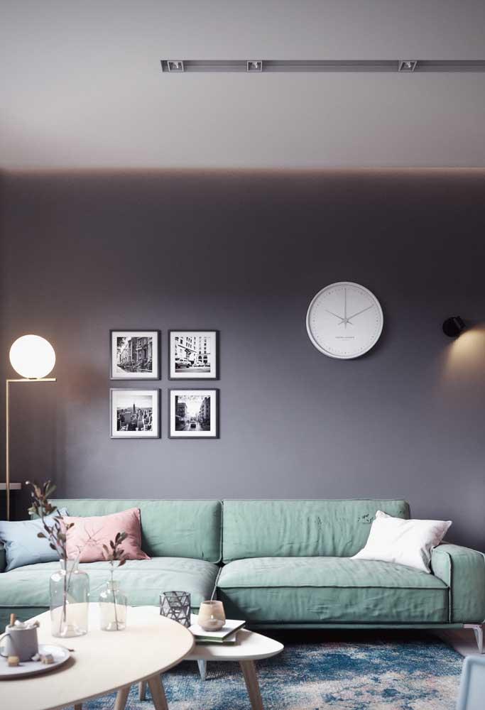 """A iluminação indireta anima o ambiente de paredes cinzas; destaque para o sofá azul esverdeado """"aquecendo"""" a sala"""