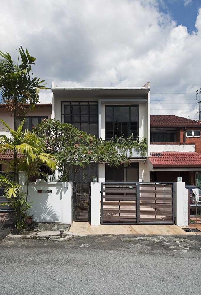 Casa sobrado com portão social e da garagem feito com modelo de grade de alumínio vazado e listras horizontais