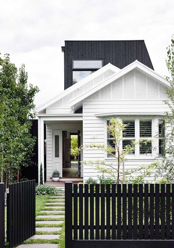 A casa simples, de modelo clássico e tradicional, apostou em uma grade de madeira baixa para delimitar o acesso ao imóvel