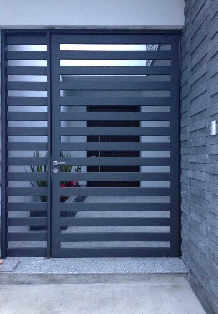 Nessa casa, os vãos entre as grades do portão de alumínio permitem que o interior da residência fique visível