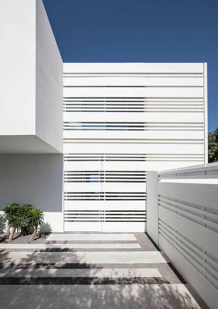 Grade alta com diferentes vãos de abertura; o resultado é uma fachada parcialmente encoberta