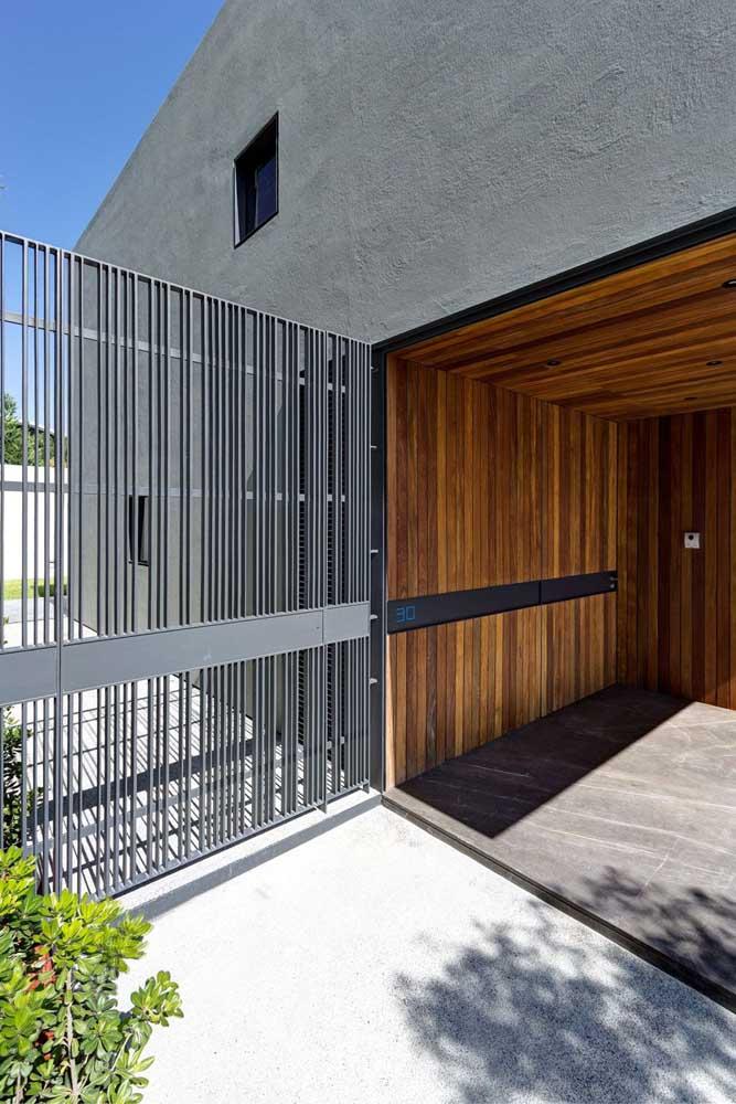 Portão automático de grade cinza; as listras verticais garantem um charme extra ao portão
