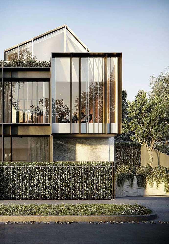 Nessa linda casa, a grade metálica que atua como muro foi praticamente toda coberta pela espécie de planta trepadeira