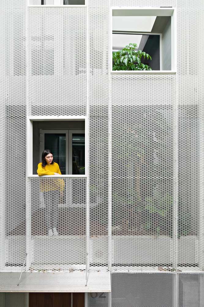 Nessa varanda de apartamento, a grade branca protege e isola o interior do exterior