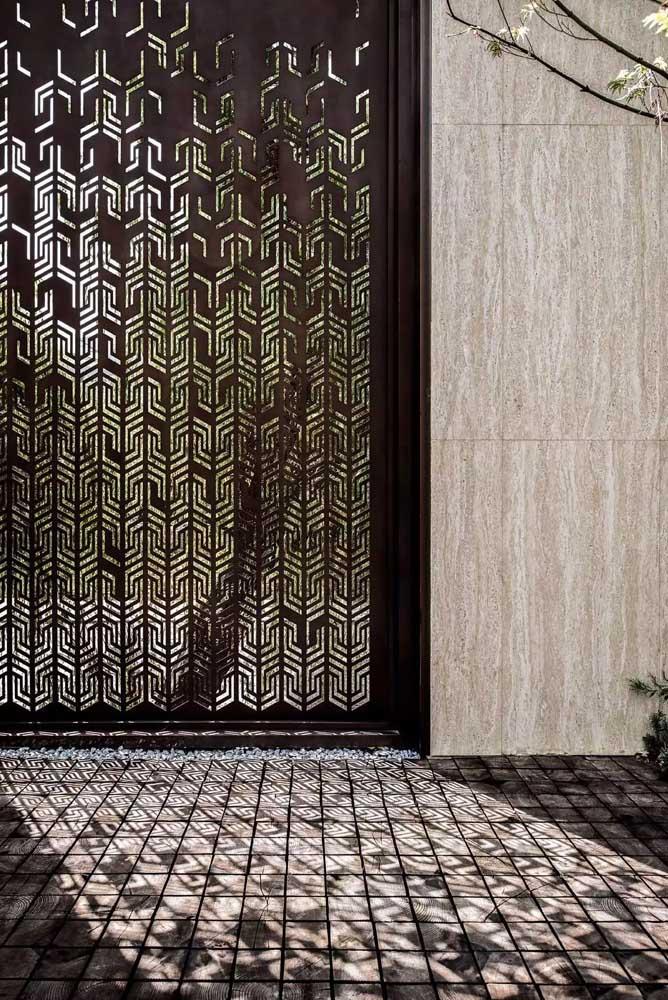 Nessa casa, o portão alto foi construído com um modelo de grade ricamente desenhado