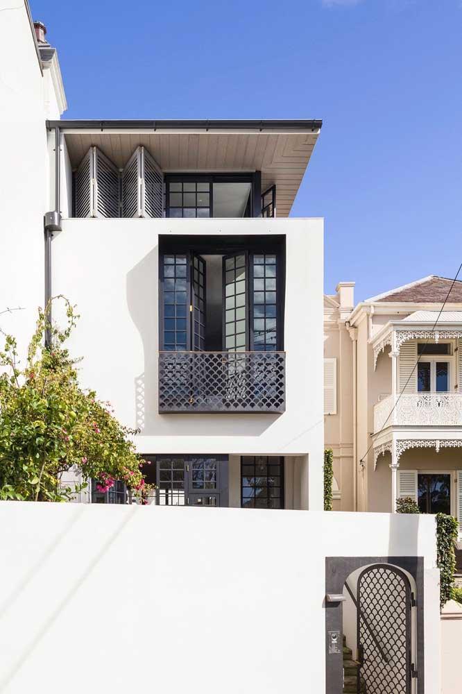 Nessa casa, o mesmo modelo de grade usado no portão segue no guarda corpo da varanda