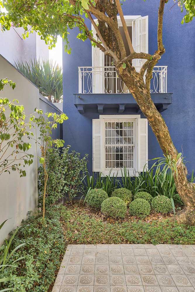 A grade branca dessa varanda forma uma combinação perfeita com as janelas de madeira na mesma cor
