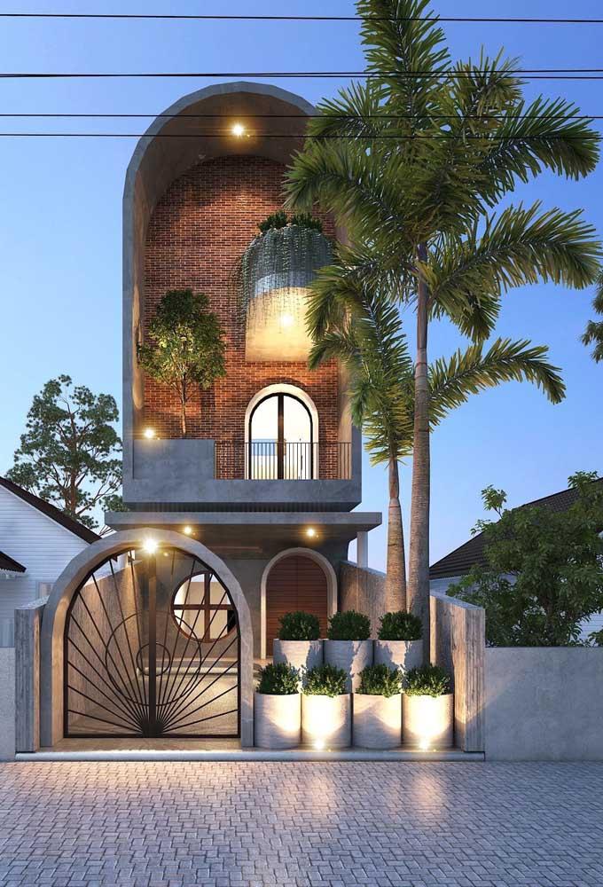 Que linda proposta! Aqui, o portão arredondado segue o mesmo estilo arquitetônico da casa