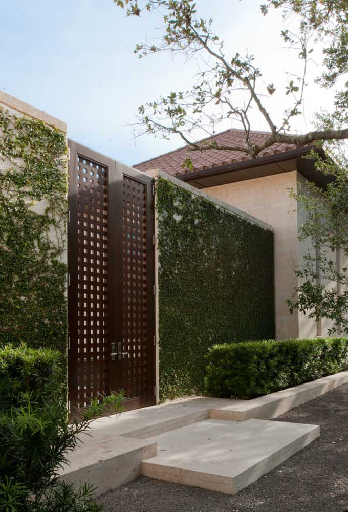 Esse portão de grade com detalhes vazados se assemelha muito a um modelo de madeira, especialmente pela cor usada no acabamento