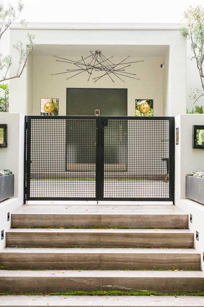 Aqui, o modelo de portão de grade baixo garante o acesso à entrada da casa