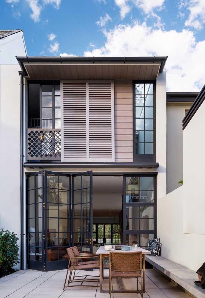 Porta de grade com vidros para delimitar os espaços externo e interno da casa