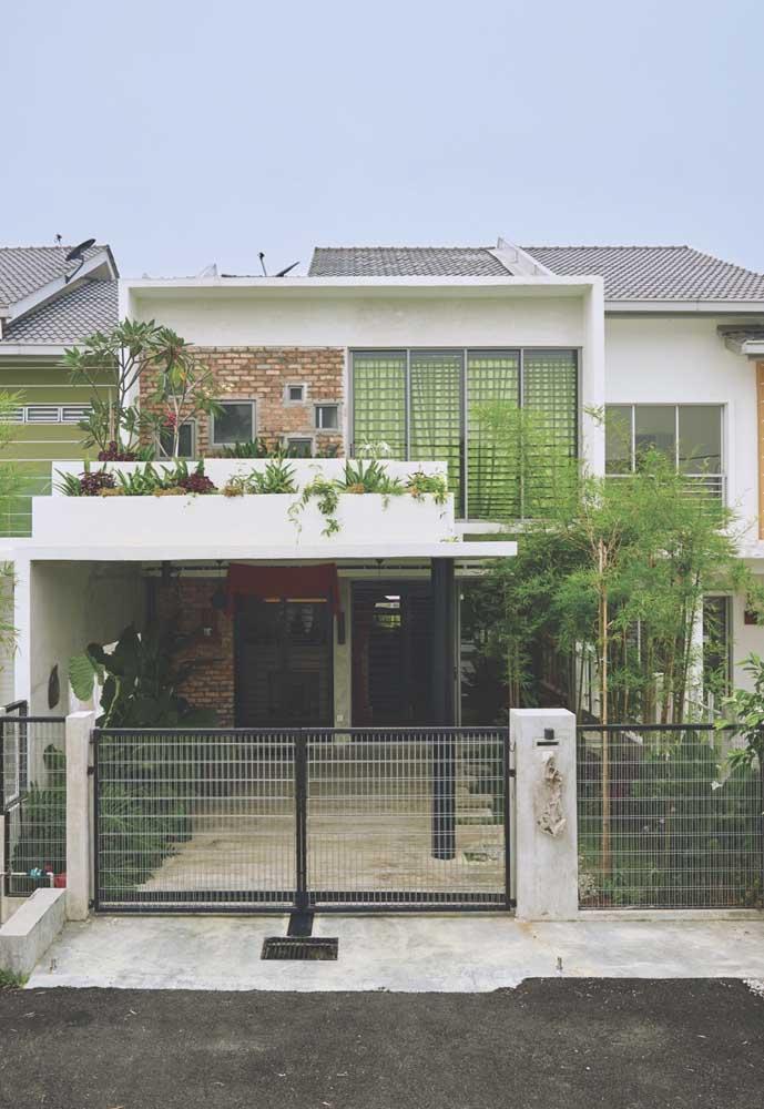 Modelo de portão com grade de ferro simples e funcional para atender a garagem e a entrada social da casa
