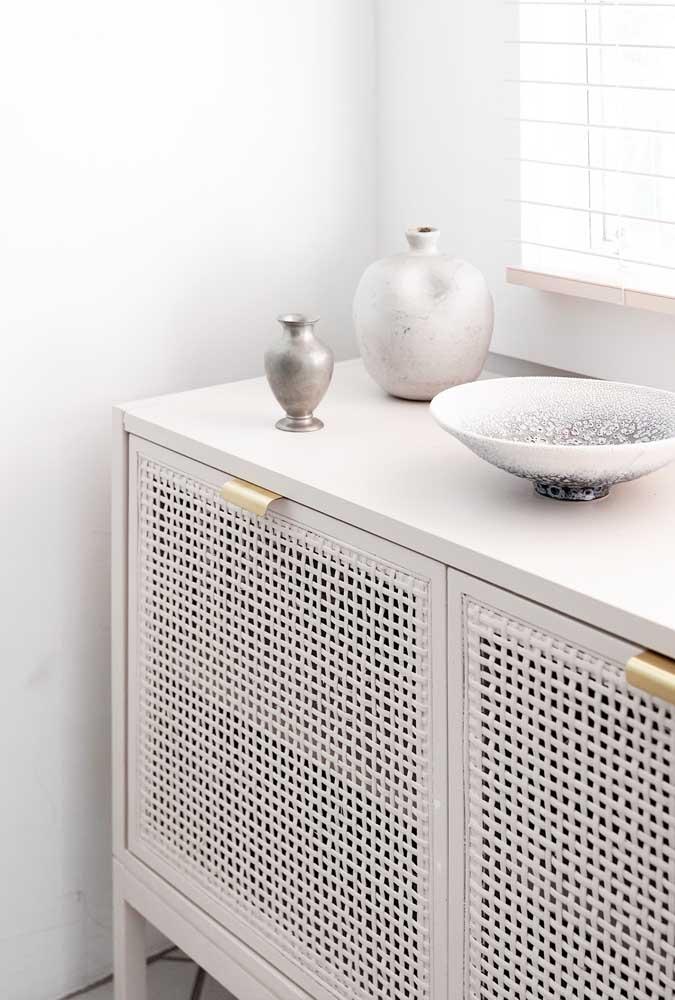 Porta de armário feita com rattan branco, os puxadores dourados completam o visual do móvel