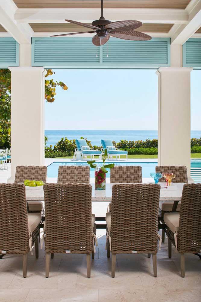 Um belo conjunto de mesa e cadeiras em rattan para a sala de jantar integrada à área da piscina