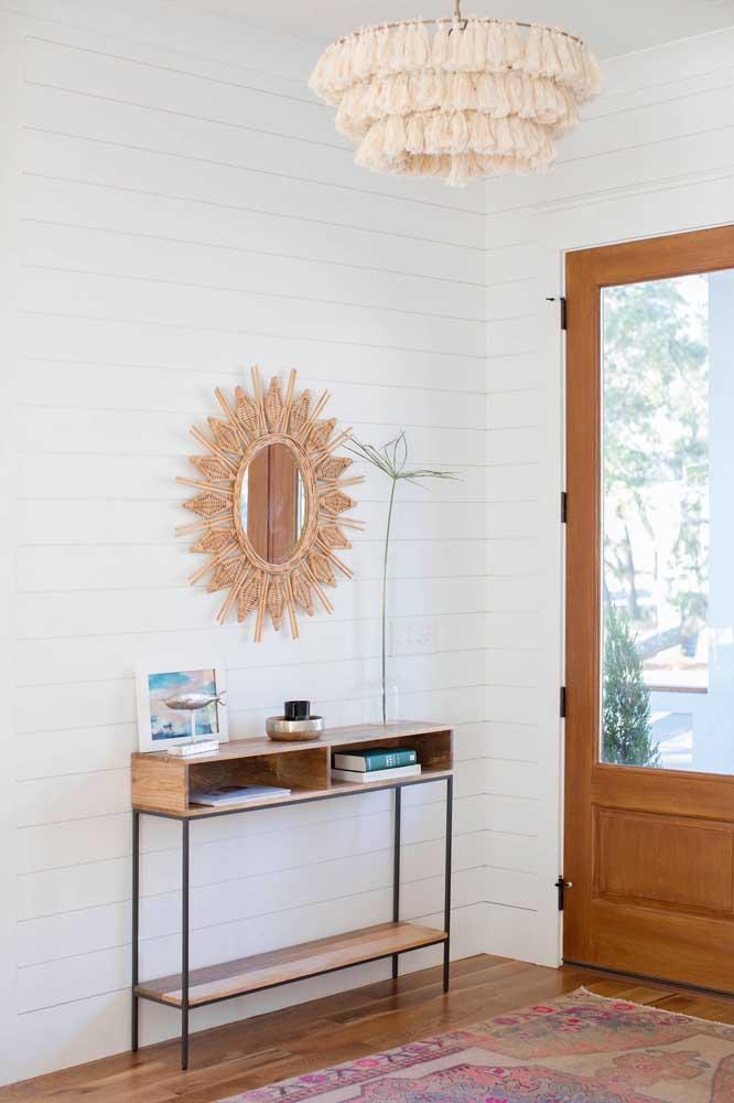 Que graça esse espelho com moldura de rattan; o destaque do hall de entrada