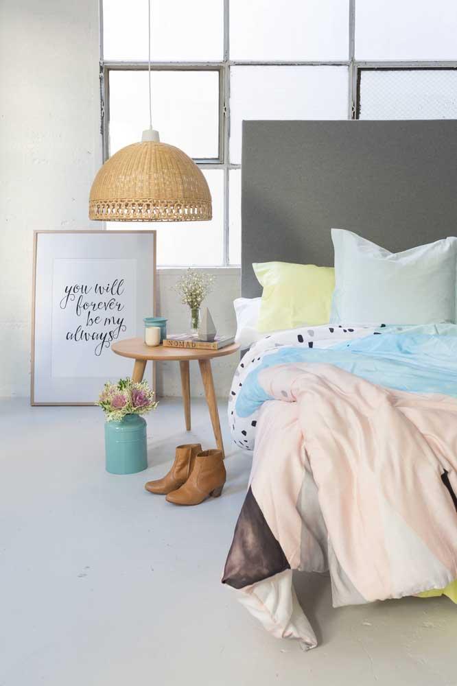A decor simples desse quarto ganhou um toque a mais com a luminária de rattan