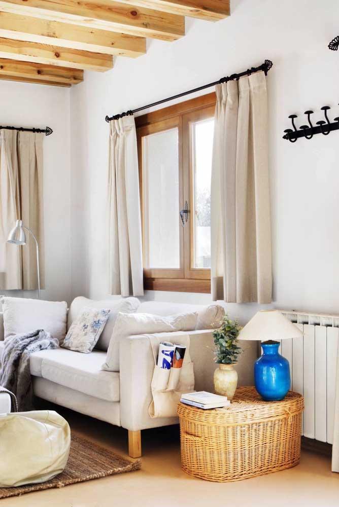Nessa sala, o baú de rattan serve para guardar objetos e também como mesinha lateral