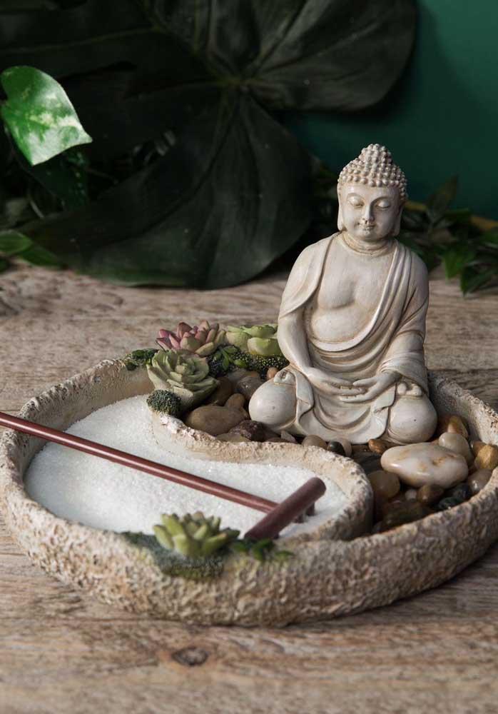 Jardim zen em miniatura com uma pequena estátua de buda, suculentas e o espaço reservado para a areia e o ancinho; repare que o recipiente de pedra onde foi construído o jardim forma o símbolo sagrado do Tao