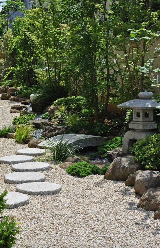 Jardim zen grande com caminho de pedras, estátuas e mini ponte