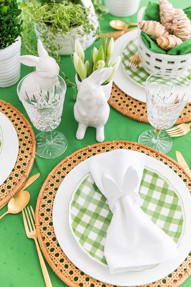 Essa mesa de Páscoa em tons de verde e branco traz pequenos coelhos de cerâmica como enfeites