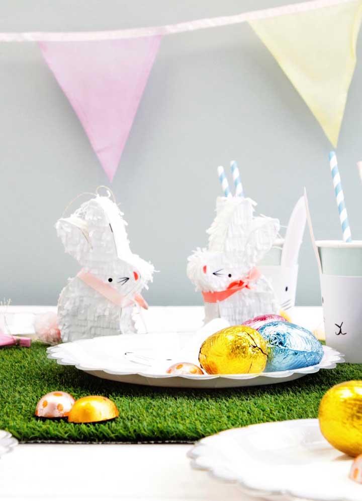 Uma gracinha esses coelhinhos de papel decorando a mesa onde se encontram os ovinhos de chocolate
