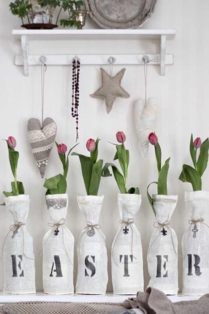 Dê uma nova finalidade para as garrafas de vidro; aqui elas escrevem a palavra Páscoa e também são usadas como vaso solitário para as tulipas