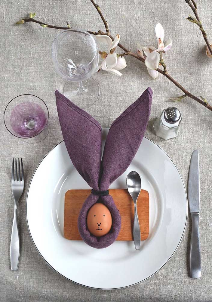Mesa posta com guardanapo dobrado em formato de coelho; destaque para o ovinho desenhado no centro