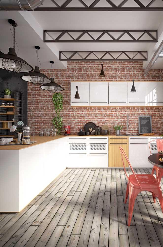 Essa cozinha moderna com toque industrial apostou em uma pequena notável no balcão aos fundos, a cafeteira; repare que ela se combina com as cadeiras da mesa de jantar