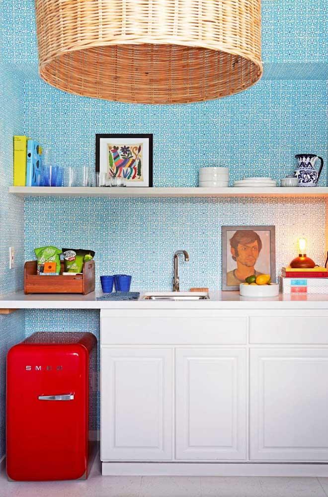 Essa cozinha cheia de estilo ganhou um frigobar vermelho retrô; destaque para o contraste entre a cor do eletro e o azul da parede