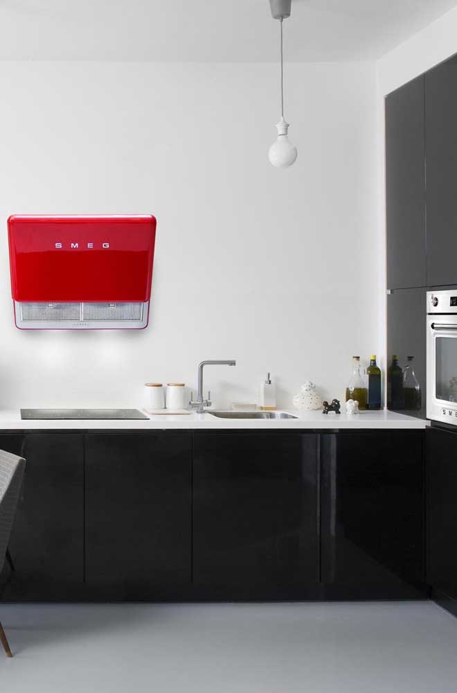A coifa vermelha moderna forma um lindo par com a cozinha de tons preto e branco