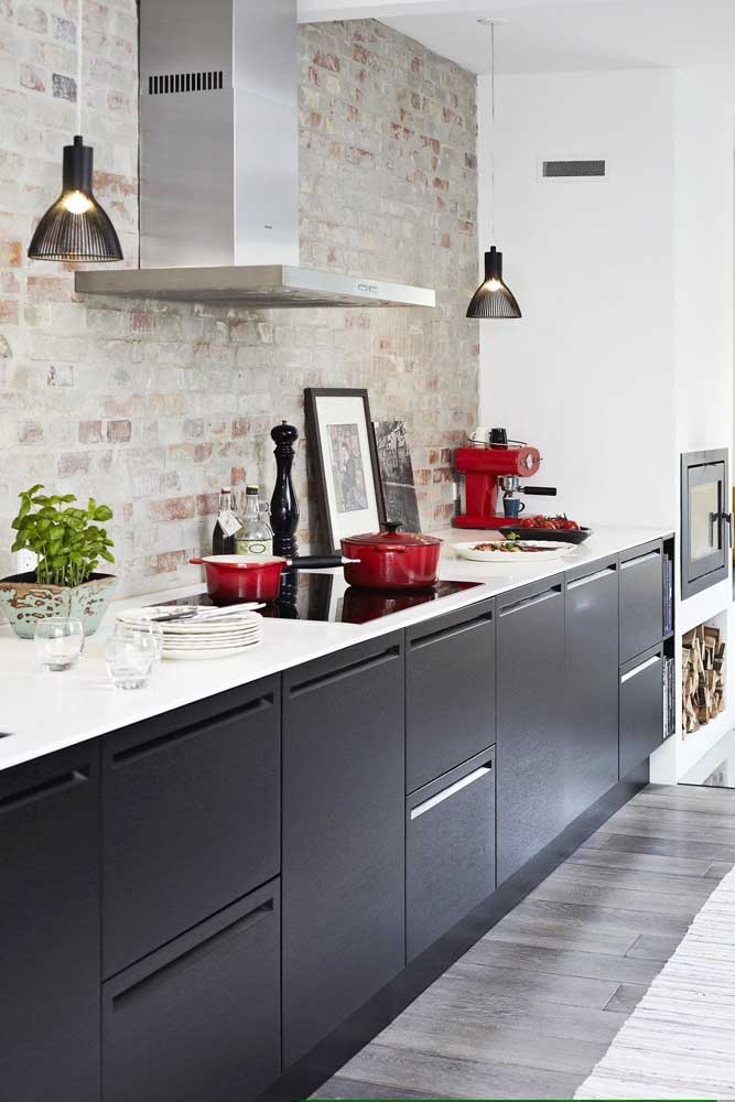 A cozinha moderna com revestimento de tijolinhos aparentes ficou mais viva e alegre com a presença da cafeteira e das panelas vermelhas