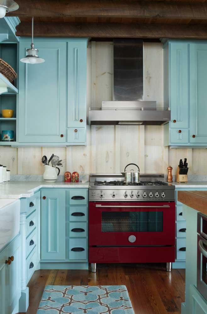 Rústico e retrô: essa cozinha super charmosa traz armários azuis de marcenaria clássica e um icônico fogão vermelho com detalhe em inox