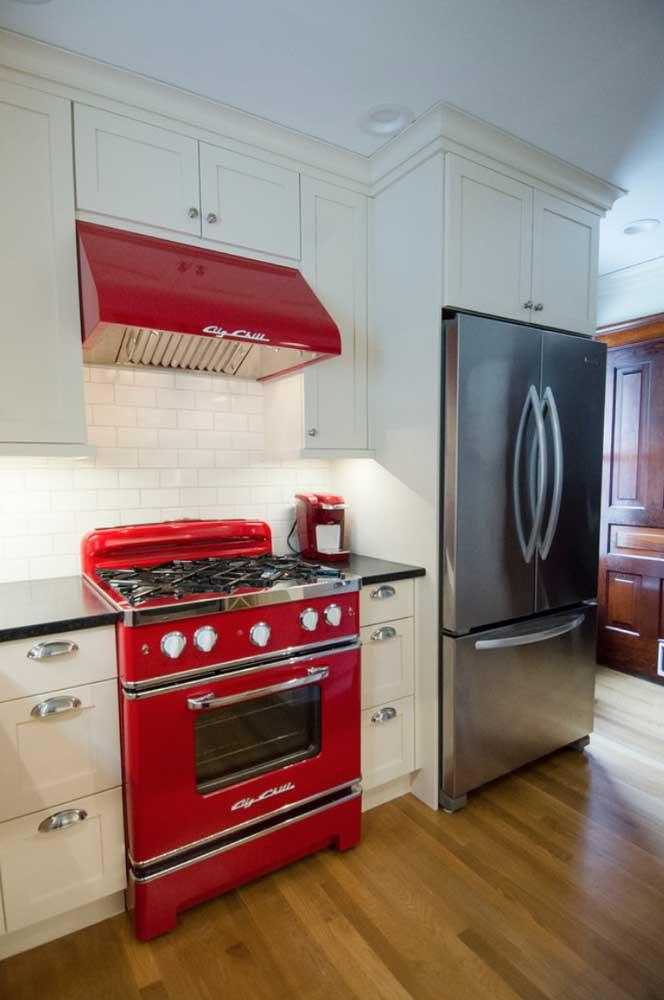Quem disse que os eletros precisam seguir sempre a mesma cor? Nessa cozinha, por exemplo, coifa e fogão são vermelhos, enquanto a geladeira é de inox