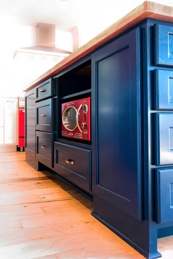 Mesmo escondido, o micro-ondas vermelho se destaca na cozinha azul marinho