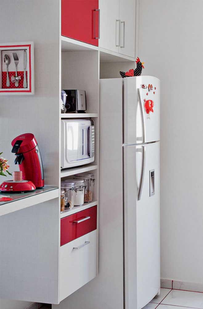 Nessa cozinha de base branca, a cafeteira vermelha é um dos pontos de destaque, juntamente com os demais detalhes na cor