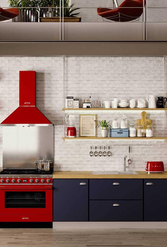 Essa cozinha de tijolinhos brancos e armários azul marinho ganhou a companhia de um fogão e coifa vermelhos; não deixe de notar também a presença graciosa do liquidificador e da torradeira