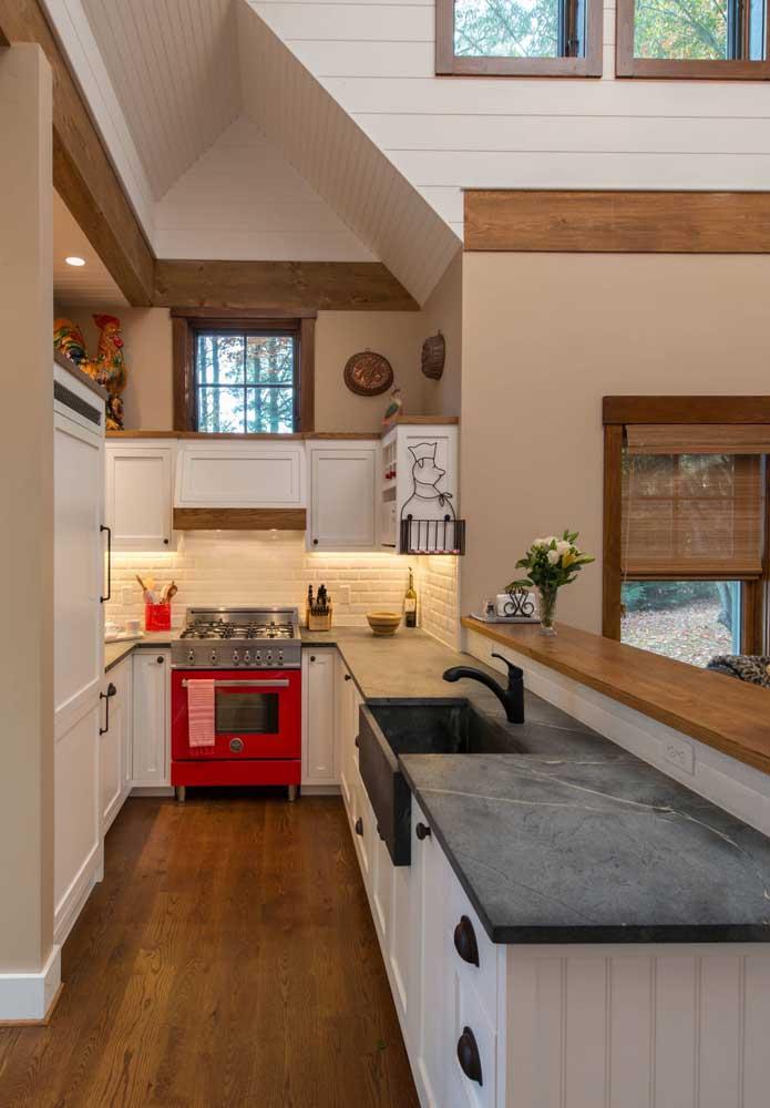 Mesmo estreita e pequena, a cozinha branca não abriu mão do fogão vermelho