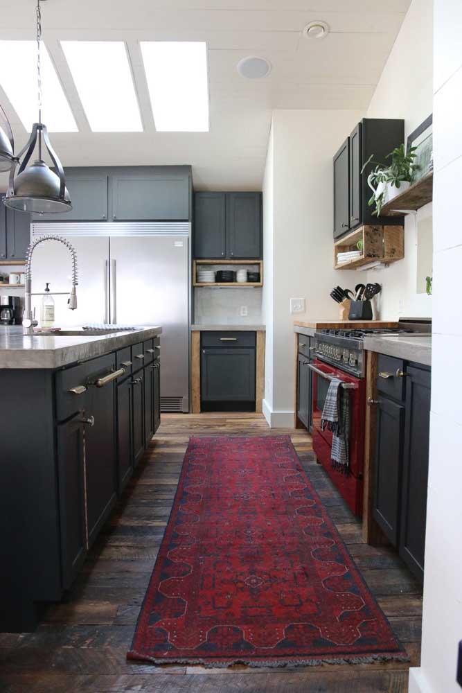 A cozinha de tons sóbrios e fechados acertou em cheio com a escolha do fogão vermelho; o tapete no mesmo tom completa a proposta