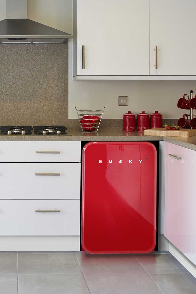 Crie pontos de cor com o vermelho em locais estratégicos da cozinha, como é o caso da imagem a seguir, em que a cor é aplicada no frigobar e em alguns objetos decorativos