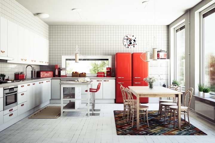 Essa cozinha ampla traz um par de geladeiras vermelhas combinando com os demais elementos na mesma cor