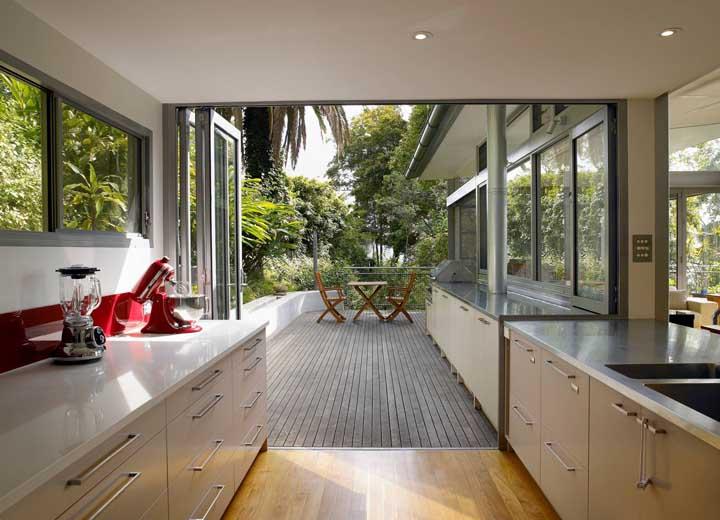 Essa cozinha simples integrada ao espaço gourmet traz um elemento de destaque na bancada: a batedeira vermelha, impossível passar despercebido por ela
