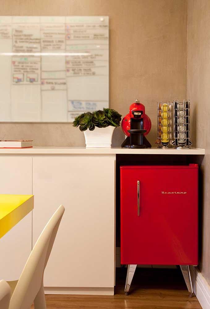 Sala de jantar com frigobar e cafeteira vermelha; destaque para o pé palito do frigobar