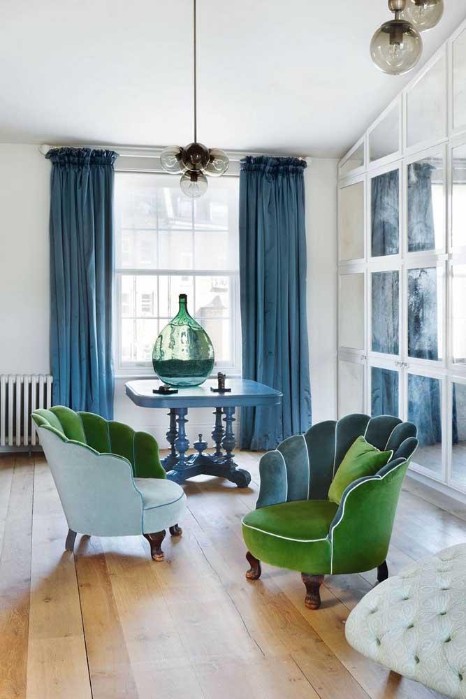 Combinação de cores análogas nessa sala de estar; o fundo branco se tornou a base para a ligação entre os tons de verde e azul que foram aplicados nas poltronas, cortina e mesa
