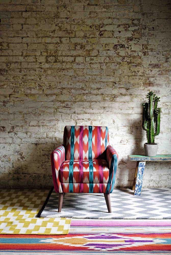 Um charme essa poltrona colorida no ambiente rústico; destaque para a sobreposição dos tapetes sob a peça