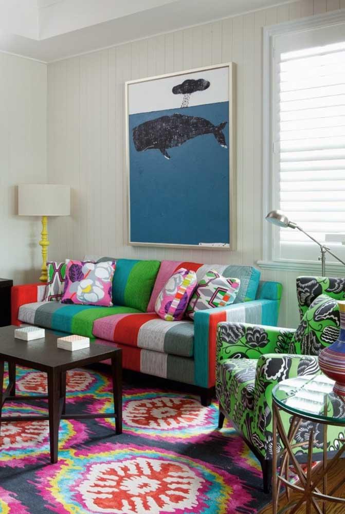 Essa sala de estar é o exemplo mor de que sofá e poltrona não precisam combinar; mas repare que o tom de verde da poltrona acompanha as listras presentes no estofado