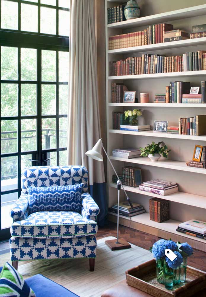 Nessa sala de estar neutra, a poltrona estampada azul virou o ponto de destaque
