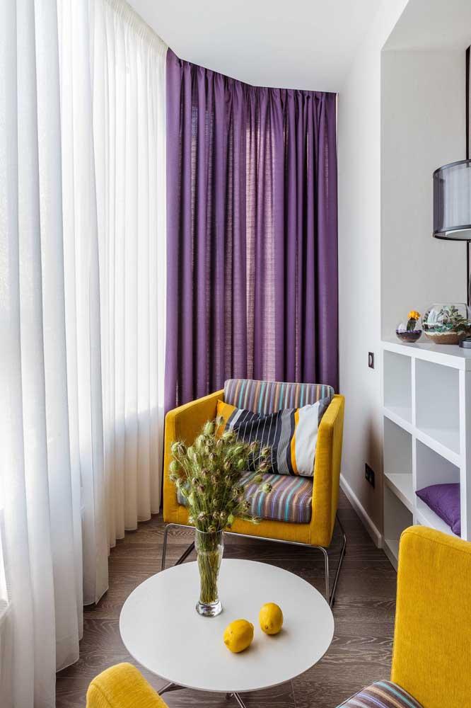 Já aqui a ideia é o inverso; a cortina roxa forma um contraste marcante com a poltrona amarela